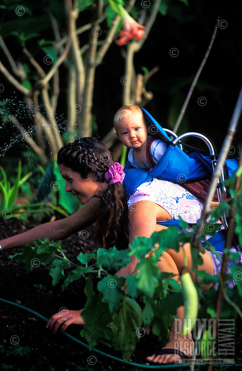 A young mother with a child on her back bends over to water her vegetable garden.