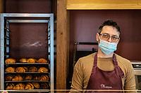 Interno di panetteria Il commesso con mascherina protettiva