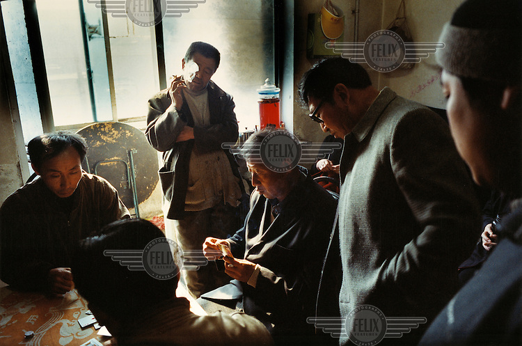 Men gambling. Millions of workers have been laid-off as China restructures its economy, slashing the bloated state-sector economy. Many have moved abroad for work.