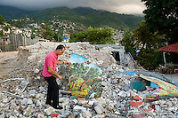 George Nadar, gallery owner, in the rubble of his museum and home afer the January 12, 2010 earthquake. He's holding a damaged painting.
