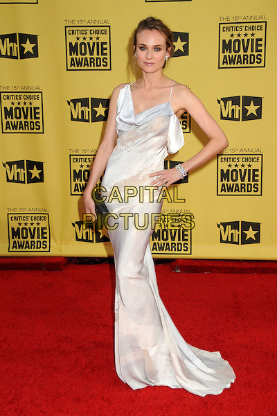DIANE KRUGER .15th Annual Critics' Choice Movie Awards - Arrivals held at the Hollywood Palladium, Hollywood, California, USA, 15th January 2010..full length long maxi dress  white cream silk  black clutch bag bracelets hand on hip.CAP/ADM/BP.©Byron Purvis/Admedia/Capital Pictures