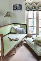 Scatter and squab cushions and a blind have been covered with fabrics in matching shades of grey and green with varieties on the same geometric pattern
