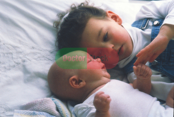 young child plays with infant in bed
