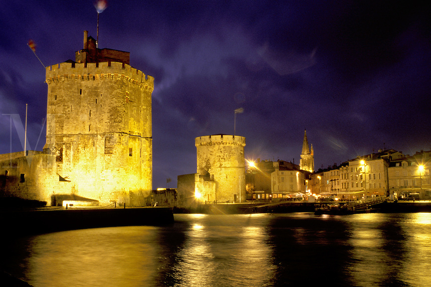 La Rochelle, France, Poitou-Charentes, Charente-Maritime, Europe, 14th century medieval stone towers illuminated at night at the entrance to the harbor of the ancient fortified old port city of La Rochelle on the Atlantic Ocean.