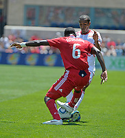 New York defender Roy Miller (7) blocks a clearance by Chicago defender Jalil Anibaba (6).  The Chicago Fire tied the New York Red Bulls 1-1 at Toyota Park in Bridgeview, IL on June 26, 2011.
