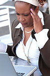 African American woman working on laptop with headache