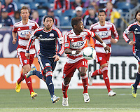 FC Dallas defender Fabian Castillo (11) brings the ball forward as New England Revolution midfielder Lee Nguyen (24) closes..  In a Major League Soccer (MLS) match, FC Dallas (red) defeated the New England Revolution (blue), 1-0, at Gillette Stadium on March 30, 2013.