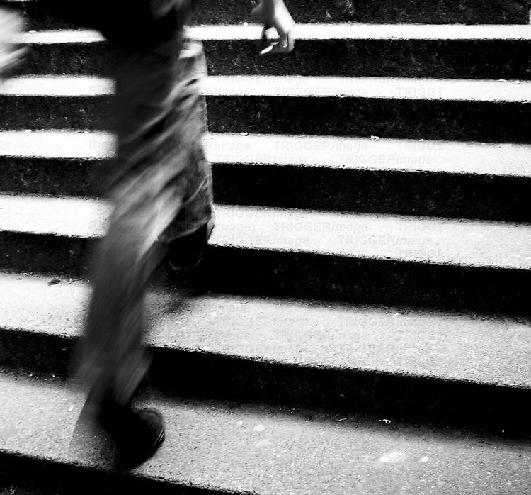 A figure holding a cigarette walking up steps