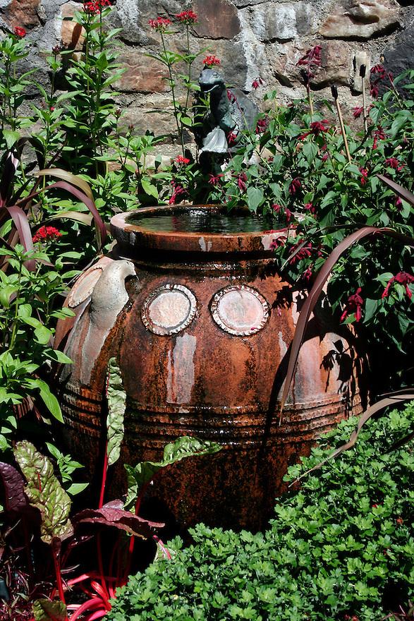 terracotta water container in lush garden