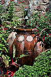 terracotta water container in lush garden