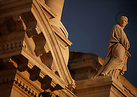Low angle view of a sculpture of a Saint, 18th century, by Ignazio Marabitti, on the facade of the Cathedral, or Duomo, Ortigia, Syracuse, Sicily, pictured on September 13, 2009, in the afternoon. The Duomo di Siracusa (Santa Maria delle Colonne) was originally built by Bishop Zosimo in the 7th century AD over the Greek Temple of Athena, 5th century BC, whose Doric columns still adorn the present facade, which was rebuilt in 1725-53 by Andrea Palma. The island Ortigia is the historic centre of Syracuse. Today the city is a UNESCO World Heritage Site. Picture by Manuel Cohen.