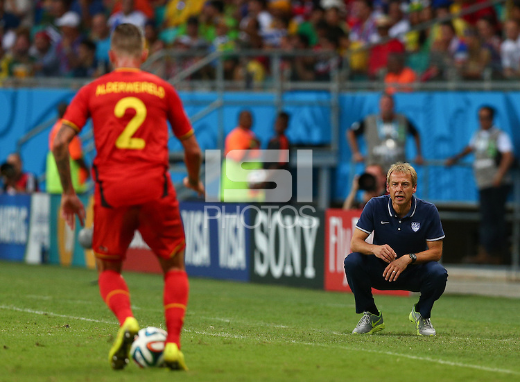 USA coach Juergen Klinsmann crouches as he watches the action from the touchline