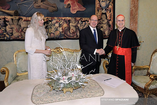 Cardinal Tarcisio Bertone,receives  Prince Albert II of Monaco and his wife Princess Charlene  at the end of a private audience in his private library at the Vatican on January 12, 2013..