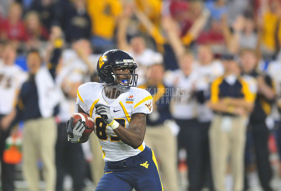 Jan 2, 2008; Glendale, AZ, USA; West Virginia Mountaineers wide receiver Tito Gonzales (83) runs for a fourth quarter touchdown against the Oklahoma Sooners during the Fiesta Bowl at University of Phoenix Stadium. West Virginia defeated Oklahoma 48-28. Mandatory Credit: Mark J. Rebilas-US PRESSWIRE