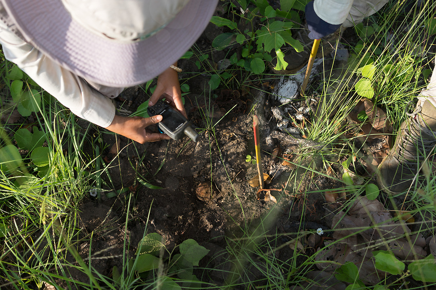 """April 26, 2017 - Banlung (Cambodia). Team leader Phorn Chan geo tags with a GPS a cluster """"bombie"""" found by one of the searcher. Finding a UXO in a designated spot means that it has to be considered contaminated and it will require the intervention of a clearing team to more thoroughly excavate the area and remove all the remnants. © Thomas Cristofoletti / Ruom"""