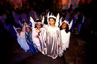 Young angels admire colored lights as they awaits their turn to parade through the streets with hundreds of citizens dressed as biblical figures during one of Holy Week's many processions in Ouro Prêto.