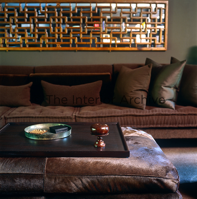 The large screen situated above the sofa in the living room is actually an antique Chinese window