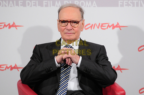 ENNIO MORRICONE.Photocall for a new book of Ennio Morricone 'Lontano da sogni', Rome Film Festival 2010, Rome, Italy..November 1st, 2010.half length black suit jacket blue tie glasses hands  .CAP/CAV.©Luca Cavallari/Capital Pictures.