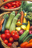 fresh summer vegetables in baskets at Tierra Vegetables farm stand with tomatoes, squash and cucumbers. Organic.