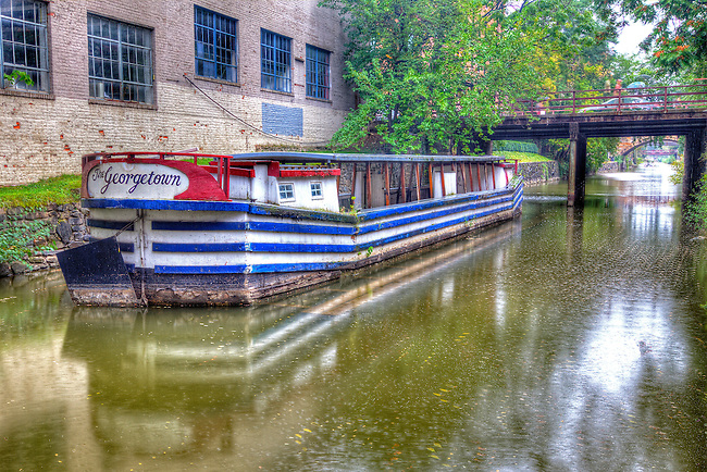 HDR image of an antiquated canal boat sitting in its own reflection with a scenic landscape backdrop.