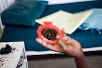 ".TB is resurgent in places like Homa Bay; places where people live in poverty. The living quarters are dark and cramped with many people sharing a single room house...HIV compromises immunity and allows TB to take hold. The living conditions contribute to its spread. The treatment for TB is complex and long...Lillian, an MSF patient, is in the hospital for a TB relapse. She is hooked up to a tube that drains the mucuss from her lungs. On her bedside table she has a small purse, purple plastic cup filled with porridge, mobile phone charger, many satchets of pills and a small red mirror...""I want to see my face, so I brought the mirror. In the morning after I wash, I look to see myself. When I looked before, I saw some fuzz from the blanket. I brushed them off and I was amused.""..Her eyes are lively, inquisitive and probing...""Before, when I looked in the mirror, I was fat and more beautiful. Today I see I am thin and not looking like myself.""."