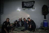 Dimitri Bontinck, a 39 years old belgium sits among Syrian rebel fighters as they pose for photo at one rebel base in Aleppo as he looks for information about Dimitri's son, a youth belgium who has turned himself into a Islamic fighter who is battling Syrian government army beside radical Muslim groups at the northern Syria.