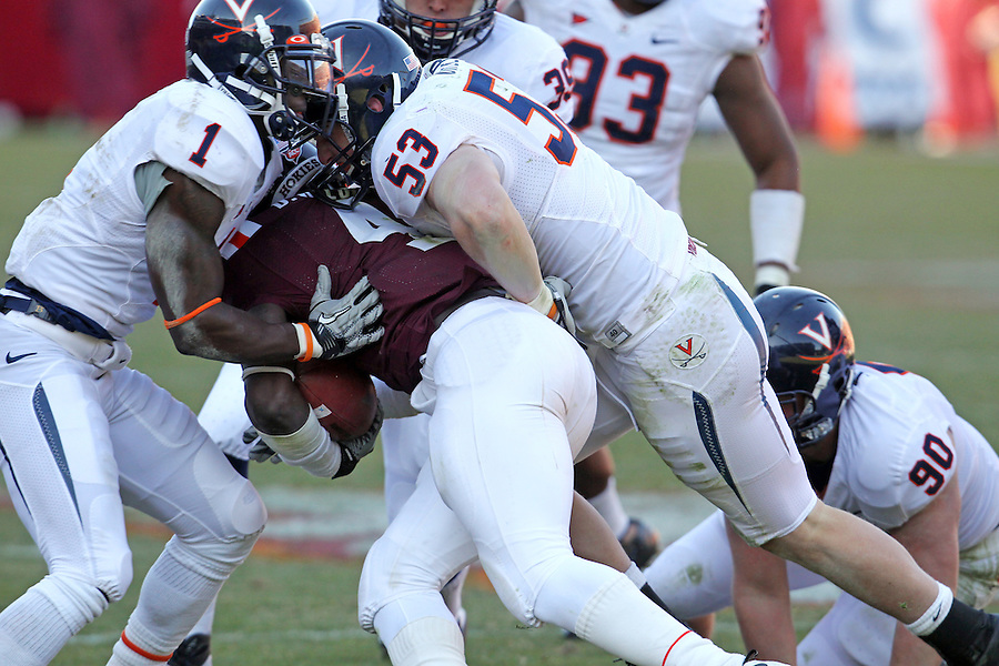 Nov 27, 2010; Charlottesville, VA, USA;  Virginia Cavaliers safety Trey Womack (1) and Virginia Cavaliers linebacker Steve Greer (53) tackle Virginia Tech Hokies running back David Wilson (4) during the game at Lane Stadium. Virginia Tech won 37-7. Mandatory Credit: Andrew Shurtleff