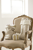 A Christmas sack and Christmas stockings containing parcels on a Louis XVI giltwood armchair