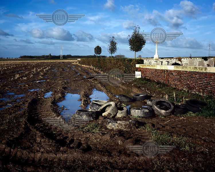 Abandoned tires in a muddy field beside the Divisional Collecting Post Cemetery and Extension near Ypres.
