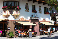 Traditional restaurant and waitress in dirndl dress in main plaza of the town of Seefeld in the Tyrol, Austria