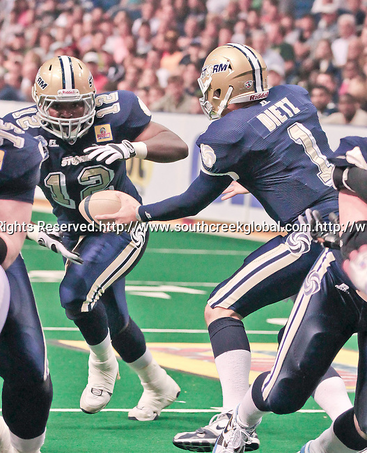 Aug 14, 2010: Tampa Bay Storm quarterback Brett Dietz (#1) hands off to fullback Terrence Royal (#12). The Storm defeated the Predators 63-62 to win the division title at the St. Petersburg Times Forum in Tampa, Florida. (Mandatory Credit:  Margaret Bowles)