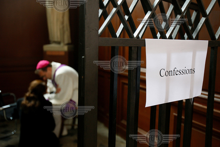 A priest takes confession during Easter week.