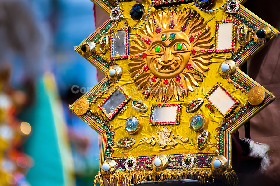 A symbol of the sun seen on a costume in the religious parade within the Corpus Christi festival in Pujilí, Ecuador, 1 June 2013. Every year in June, thousands of people gather in a small town of Pujili, high in the Andes, to celebrate the Catholic feast of Corpus Christi. Introduced originally during the Spanish conquest of South America, this celebration merges Catholic rituals of Holy Communion with the traditional Andean harvest and sun festivities (Inti, the Inca sun god). Women dancers perform wearing brightly colored costumes while men dancers wear chest ornaments and heavy elaborate headdresses adorned with mirrors, jewelry, or natural items (shells). Being a dancer in the Corpus Christi ceremonial parade (El Danzante) is considered an honour and a privilege by the indigenous people in Ecuador.