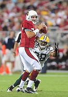 Aug. 28, 2009; Glendale, AZ, USA; Arizona Cardinals quarterback (7) Matt Leinart looks for a receiver under pressure from Green Bay Packers cornerback (38) Tramon Williams during a preseason game at University of Phoenix Stadium. Mandatory Credit: Mark J. Rebilas-