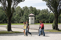 Germany. Bayern state. The Dachau Concentration Camp Memorial Site. A group of young men and women walk along the central axis of the camp which was the main camp road, along which the barracks were built on both the left and the right. The former location of the other 32 baracks are marked by foundations. The ground plan of the camp, still recognizable today and characterized by its symmetrical alignment and functional divisions, was also used in almost all other concentration camps. The impression generated by the grounds today does not reproduce the oppressive confinement and density of the barrack facilities: originally designed to hold approx. 6,000 prisoners, the camp was constantly overcrowded in the final years. On march 22, 1933, the first concentration camp was opened in Dachau by the Nazis. It became a model for all later concentration camps established under the control of the SS men and the Third  Reich. © 2007 Didier Ruef