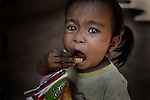 Little girl with dirty hands, eating junk food, near Luang Prabang, Laos.