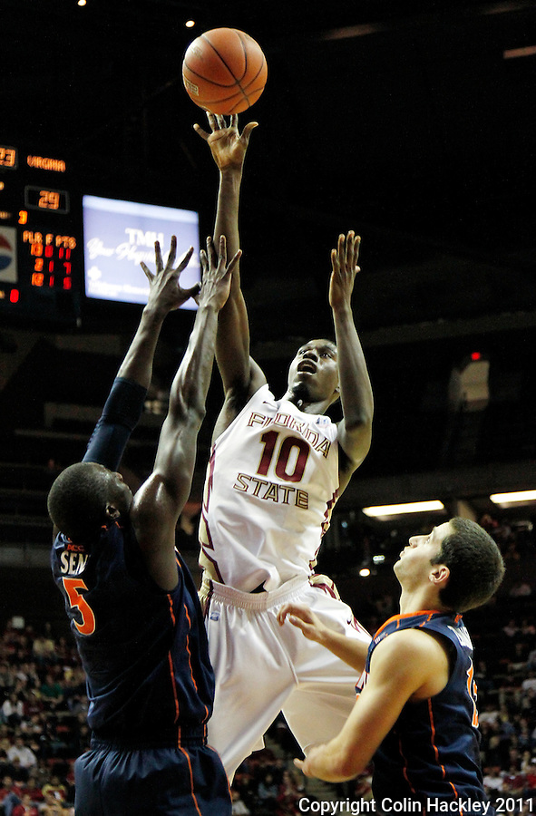 TALLAHASSEE, FL 10-FSU-VA MBB11 CH-Florida State's Okaro White shoots between Virginia's Assane Sene, left, and Sammy Zeglinski during second half action Saturday at the Donald L. Tucker Center in Tallahassee. The Seminoles beat the Cavaliers 63-56...COLIN HACKLEY PHOTO
