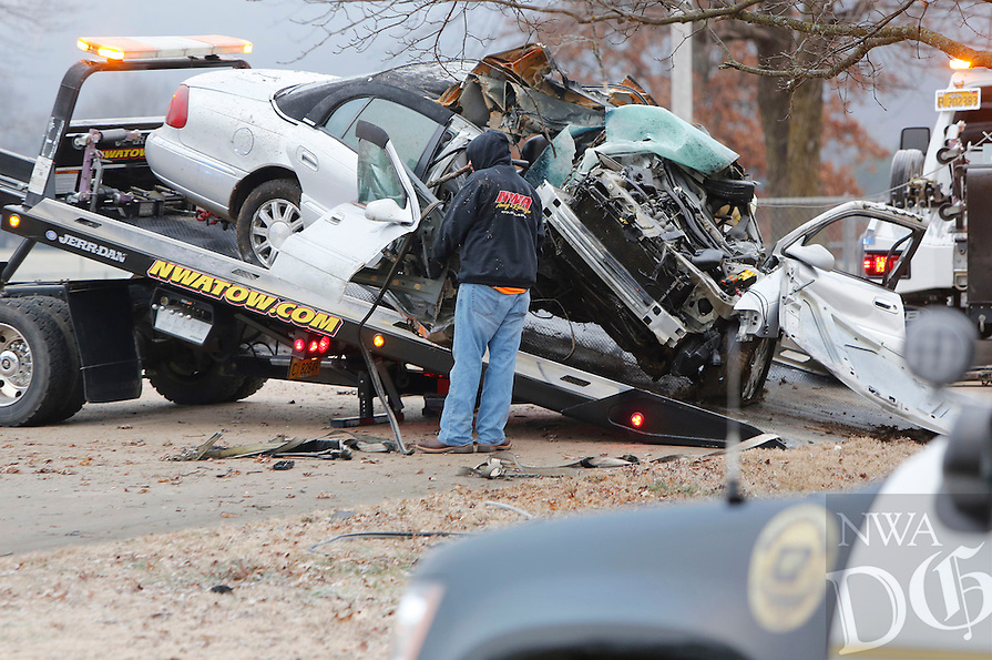 NWA Democrat-Gazette/DAVID GOTTSCHALK  The Fayetteville Police Department and NWA  Towing & Recovery prepare to transport a vehicle Monday, January 4, 2016, from the front yard of a residence near the 4500 block of Huntsville Road in Fayetteville. The vehicle was involved in a one car fatal accident.