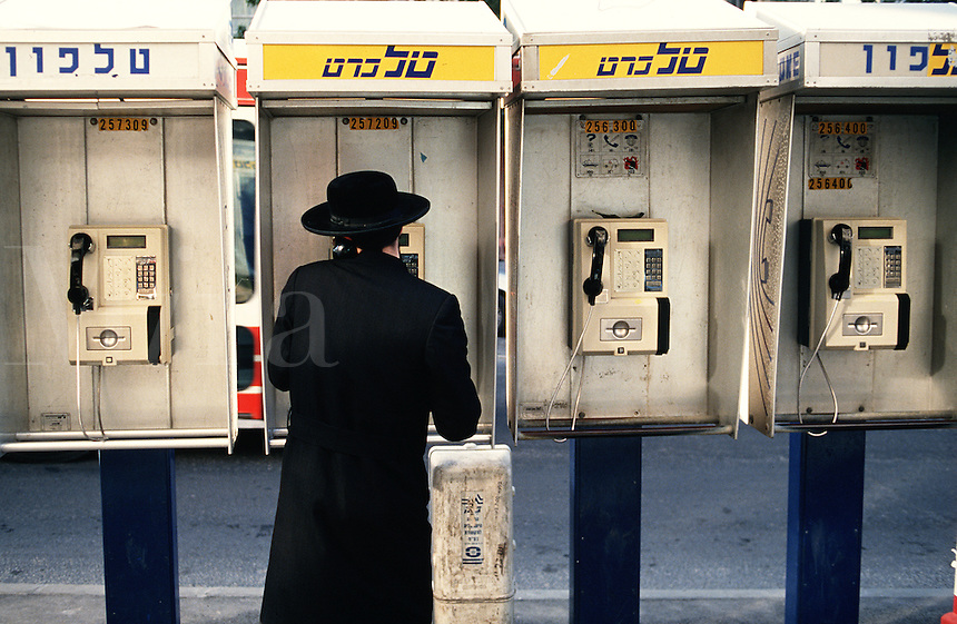 A Hasidic man using an Israeli pay phone - Hebrew lettering runs across the top. Jerusalem, Israel.