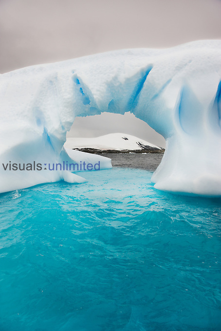 An arch formed as seawater gradually eroded this iceberg near the Lemaire Channel of Antarctica. The blue color indicates its glacial origin. Also note the three states of water: liquid (ocean), solid (iceberg), and gas (cloud).