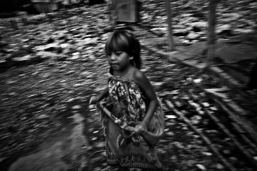 A Cambodian girl runs through a cummunity destroyed by a fire in Tuol Kork district's Boeung Kak 2 commune, Phnom Penh, Cambodia, June 4, 2010.