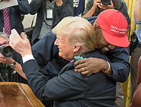 Kanye West hugs United States President Donald J. Trump hugs they meet with Jim Brown in the Oval Office of the White House in Washington, DC on Thursday, October 11, 2018.<br />