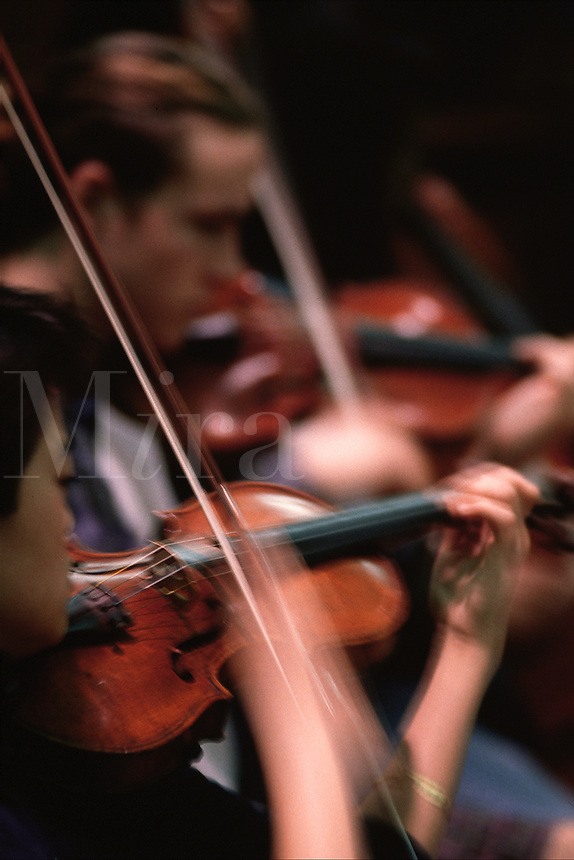 Blurred image of the violin section of a youth orchestra in motion.