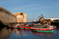 Traditional wooden fishing boats in the harbour with the defensive walls of the Portuguese Fortified city of Mazagan in the background (left) and a flotsam (right), El Jadida, Morocco. El Jadida, previously known as Mazagan (Portuguese: Mazag√£o), was seized in 1502 by the Portuguese, and they controlled this city until 1769. Picture by Manuel Cohen