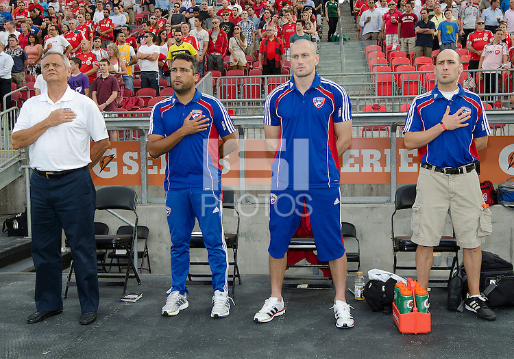 FC Dallas head coach Schellas Hyndman and his coaching staff stand at attention during the national anthems in an MLS game between the FC Dallas and the Toronto FC at BMO Field in Toronto on July 20, 2011..FC Dallas won 1-0.