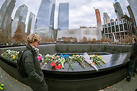 Visitors to the National September 11 Memorial & Museum in New York on Christmas, Thursday, December 25, 2014. The memorial consists of twin memorial pools on the footprints of the World Trade Center and a plaza planted with more than 400 swamp white oak trees. The names of the 2983 victims of 9/11 and the February 1993 WTC attack are inscribed around the base of the pools. (© Richard B. Levine)