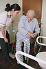 Female occupational therapist assessing elderly patient's mobility and independence by observing toilet transfer,