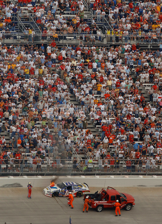 Sept. 24, 2006; Dover, DE, USA; Nascar Nextel Cup driver Scott Riggs (10) stands near his burning car after crashing during the Dover 400 at Dover International Speedway. Mandatory Credit: Mark J. Rebilas