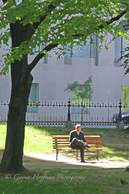 A man sitting on a park bench in the sun. Leg crossed, wearing a suit.