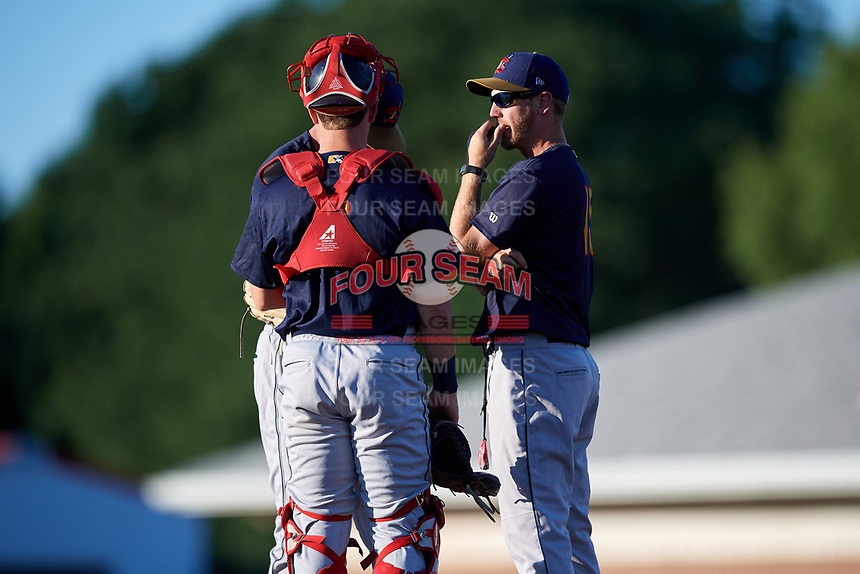 State College Spikes pitching coach Adrian Martin (15) talks with starting pitcher Chris Holba (50) and catcher Matt Duce (8) during a game against the Batavia Muckdogs on July 7, 2018 at Dwyer Stadium in Batavia, New York.  State College defeated Batavia 7-4.  (Mike Janes/Four Seam Images)